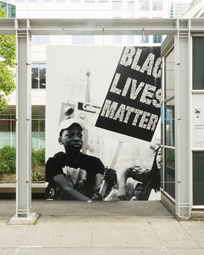 A young marcher holds a 'Black Lives Matter' sign during a 2015 action by Black Lives Matter Toronto. © Jalani Morgan